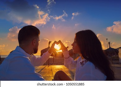 Couple young heart symbol with hands at the beach vacation sunrise in Spain