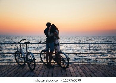 Couple of young hipster lovers hugging at the beach and watching the sunrise at wooden deck summer time