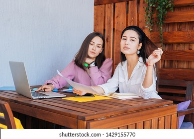 Couple of young kazakh businesswomen are designing new office bilding for their company. Two attractive designers are downloading some files while sitting in the cafeteria after productive weekdays