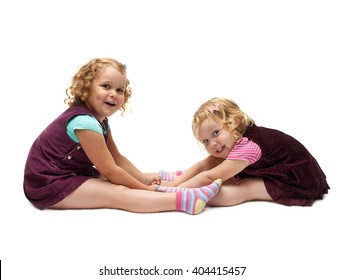 Couple of young little girls sisters with curly hair in purple dress sitting over isolated white background