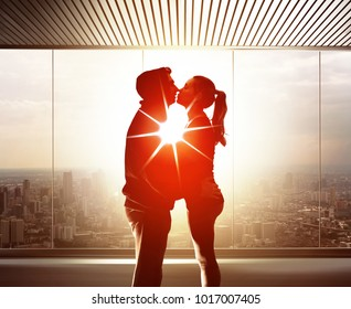 couple of young lovers embrace and kiss each other at sunset