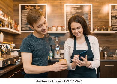 Couple of young male and female coffee shop owners near the counter, talking and smiling, coffee shop business concept.