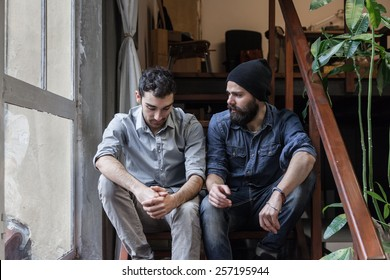 Couple of young men talking on the stairs of an office