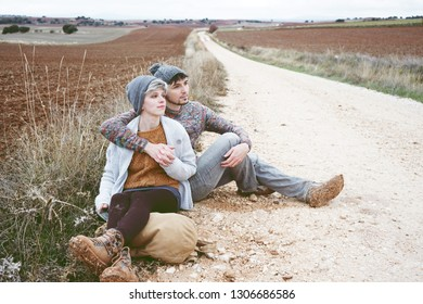 Couple of young millennials hugging and resting by a backpack in an adventure trip on a outdoor country path