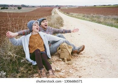 Couple of young millennials hugging and shouting by a backpack in an adventure trip on a outdoor country path
