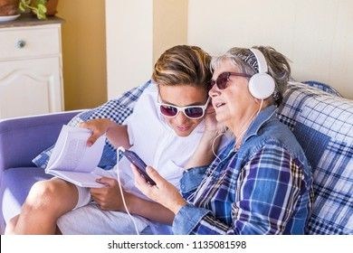 couple young and old grandmother and teenager nephew family time together listen music with earphones and enjoy the day. Happy family and generations different ages concept