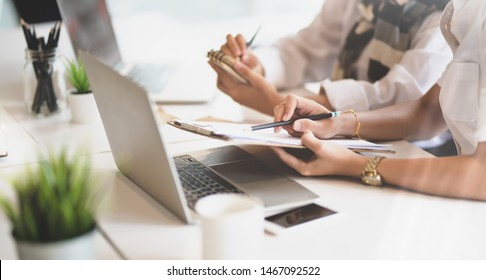 Couple of young passionated businesswomen discussing their projects together with laptop computer