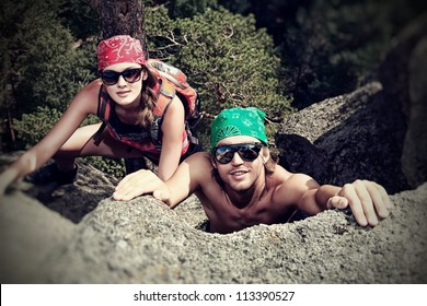 Couple of young people alpinists are climbing on a mountain.