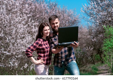 Couple of young people looking in laptop standing in a blooming spring park