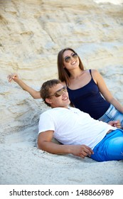 Couple of young people lying on the beach