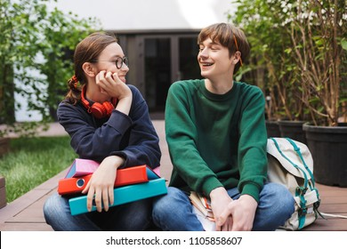 Couple of young smiling students sitting with colorful folders and books in hands and happily looking on each other while spending time together in courtyard of university