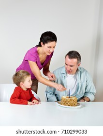 Couple and young son with birthday cake