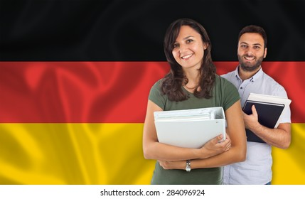 Couple of young students with books over german flag