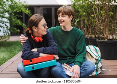 Couple of young students sitting with colorful folders and books in hands and joyfully looking on each other in courtyard of university