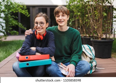 Couple of young students sitting with folders and books in hands and joyfully looking in camera while spending time together in courtyard of university