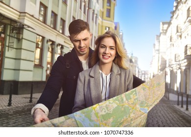 Couple of young tourists reading a map in the city
