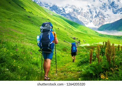 Couple of young travelers hiking with backpacks on beautiful grassy trail in Alps mountains