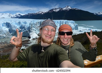 Couple of young travelers in Patagonia, glacier and mountain in background, selfie style
