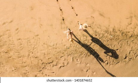 Couple of young woman have fun at the beach in summer holiday vacation at the resort - vertical top view and nice shadows - people having fun together in friendship - sandy lifestyle