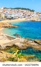 Couple of young woman in swimsuits on amazing beach in Calella de Palafrugell, scenic fishing village with white houses and sandy beach with clear blue water, Costa Brava, Catalonia, Spain