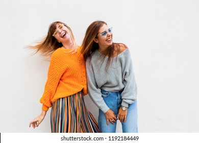Couple of young women having fun together.  Windy hairs. Two girls fooling around and dancing on white background.  Warm knitted sweater. Stylish glasses.