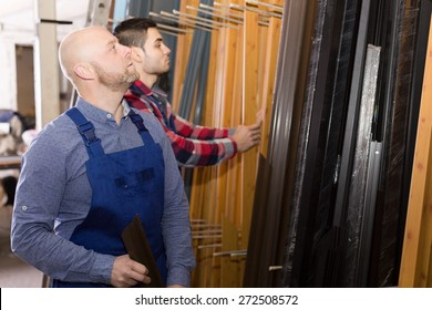 Couple of young workmen inspecting window frames at factory