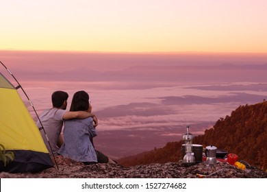 Couples, boys and girls, friends hugged the tent area, there is a tent with cooking equipment, coffee ,tea on the hillside, watching the morning sun rise, the fog faded.