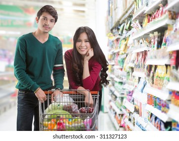 Couples are choosing food at the supermarket .They are smiling