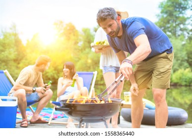 Couples drinking beer and having fun on barbeque picnic in pier at lake with yellow lens flare