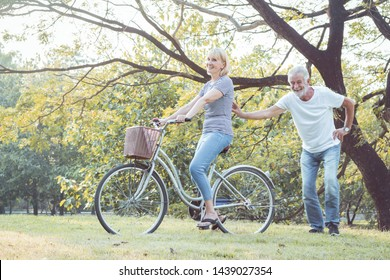 Couples elderly are bicycling together in the park. Couples elder play a bike together happily and fun. Concept of couples elderly good healthy and strong.