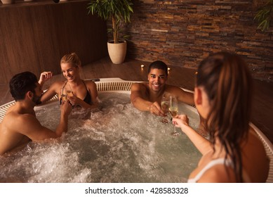 Couples enjoying day in jacuzzi together.