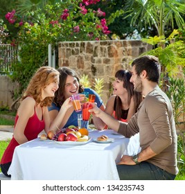 Couples enjoying a healthy outdoor lunch. Couples enjoying a healthy outdoor lunch in the garden laughing and joking as they toast each other with their drinks