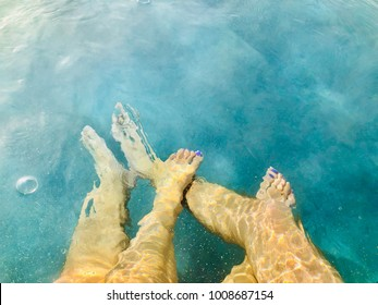 Couples Feet in Hot Tub Jacuzzi Spa Outdoors Top View Romantic Getaway