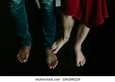 Couple's feet on the black wooden floor