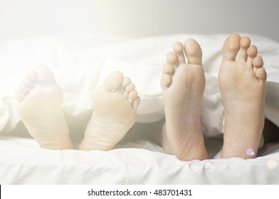 Couples feet outside the bed