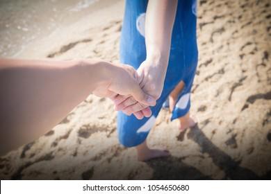 The couple's hands on the beach.