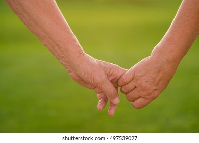 Couple's hands on green background. Hands of two seniors. Not a step without you. Don't let go.