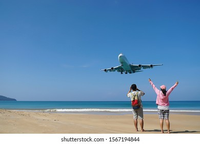 Couples have fun on the beach watching the landing planes. Traveling on an airplane concept. Amazing landscape.