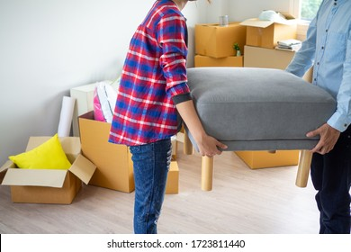 Couples helping each other to move personal belongings lifting furniture into the house. House moving ideas.