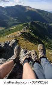 Couple's legs together on the rock on top of the mountain by the cliffside with mountain ridge on the background. Hikers boots. Summer time