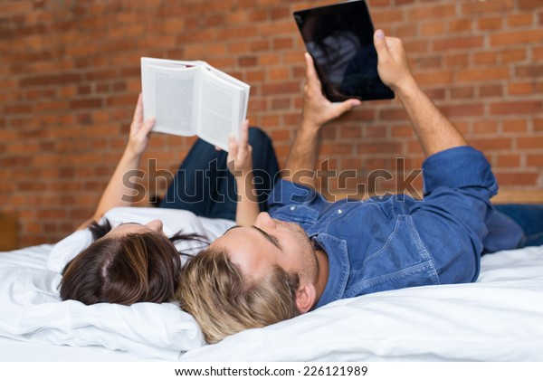 Couples Lying on White Bed while Girlfriend Reading a Book and Boyfriend Using Tablet.