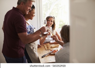 Couples make a toast while preparing food, view from doorway