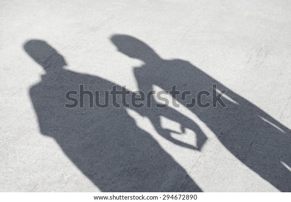 A couples shadow holding hands to form a heart