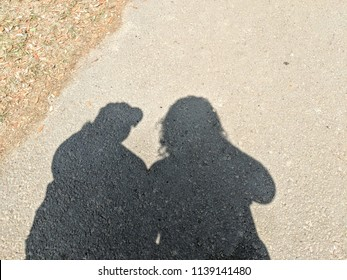 Couple's shadows in the sand
