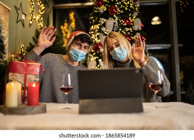Couples sit in front of their laptops with Corona masks on Christmas and greet their family in a video call. - Shutterstock ID 1865854189