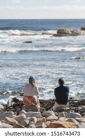 A couples are sitting on the rocks at cape of good hope, Cape Town, South Africa
