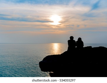 Couples are sitting to see sunset on cliff