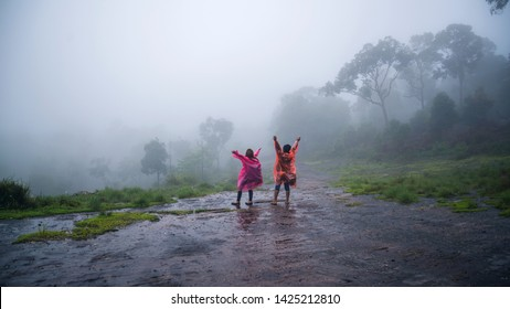 couples tourist with rain coat walking travel adventure nature in the rain forest. travel nature, Travel relax, Travel Thailand, rainy season, Happy, romantic.