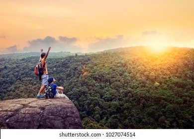 couples of traveling man and woman relax on top of  high mountain with beautiful sunset sky behind green mountain
