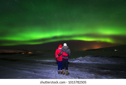 couples are watching the night sky aurora dancing